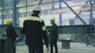 Engineer in hardhat is greeting workers with a handshake at a heavy industry factory. video