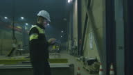 Engineer in hardhat is moving through a heavy industry factory with a tablet computer. video