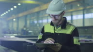 Engineer in hardhat is using a tablet computer in a heavy industry factory. video