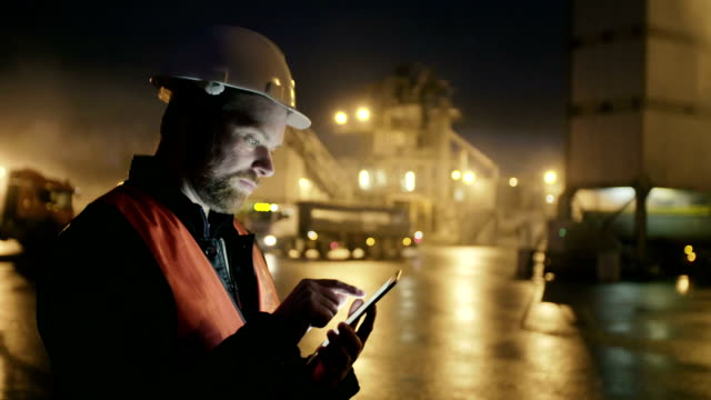 Engineer in hardhat with a tablet computer looks at truck on heavy industry factory video