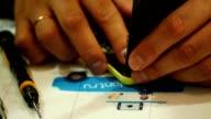engineer mount new display on smartphone, during cellphone repair video