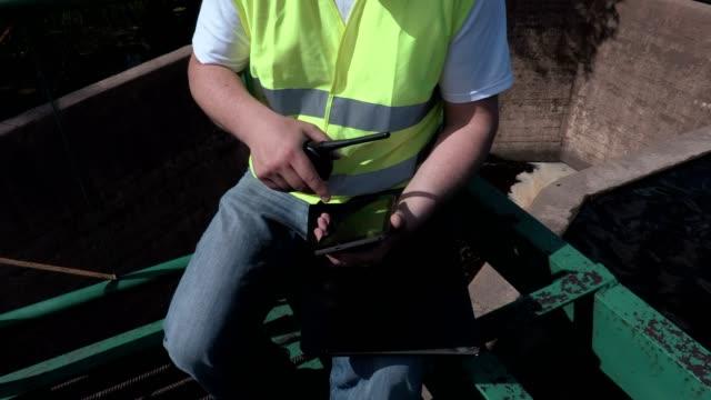 Engineer on the walkie-talkie using tablet on floodgate video