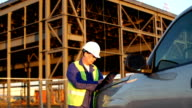 Engineer or job superintendent uses a tablet on construction site video