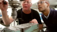 Engineer Showing Apprentice How To Operate Drilling Machine video
