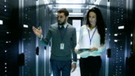 IT Engineer Shows Working Data Center/ Server Room to Female Chief Engineer who Holds Tablet Computer. video