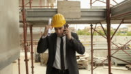 Engineer talking on mobile phone and walking in construction site video