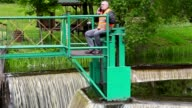 Engineer talking on smart phone at floodgate video
