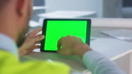 Engineer using Tablet Computer with Green Screen inside Building Under Construction. Great for Mockup usage. video