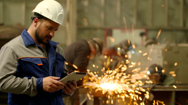 Engineer using Tablet PC in in heavy industry factory. Grinding sparks background video
