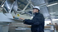 Engineer Wearing Hard Hat Setting Up CNC Machine at the Factory video