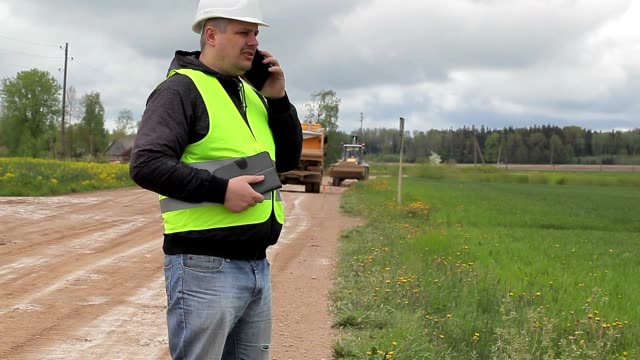 Engineer with cell phone in road repairs video
