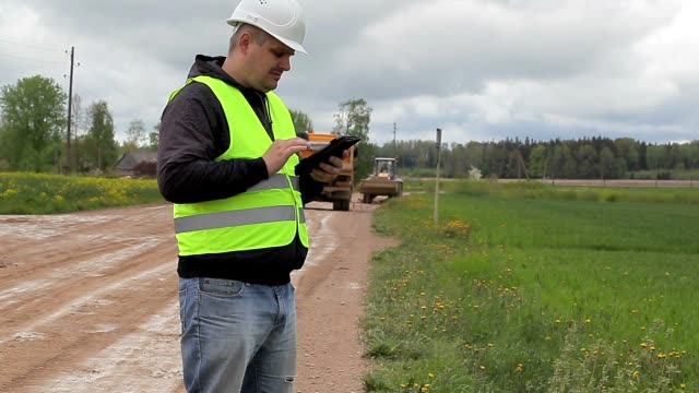 Engineer with tablet PC in road repairs video