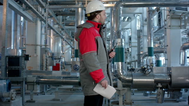 Engineer working in a thermal power plant with talking on the walkie-talkie for controlling work video