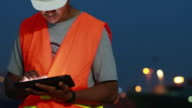 Engineer working using digital tablet with as a Cargo port background at night video