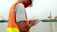 Engineer working using digital tablet with as a Cargo port background video