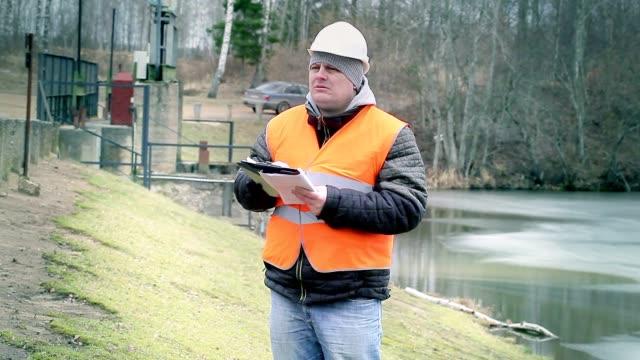 Engineer writing documentation at power plant sluice video