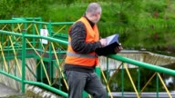 Engineer writing near floodgate video