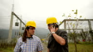 Engineers in front power station using phone video