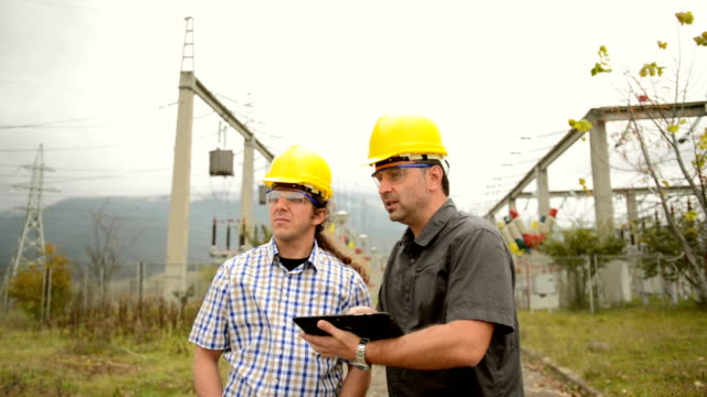 Engineers in front power station using tablet video