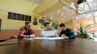 Engineers sit at round wooden table and discuss project video