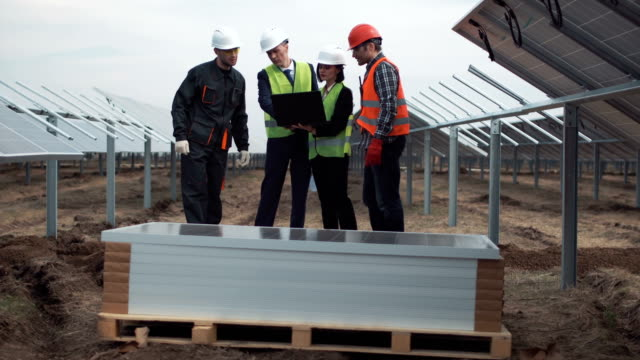 Engineers with blueprint and laptop on solar farm video