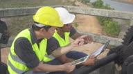 4K DOLLY MS : Engineers work at floodgate video