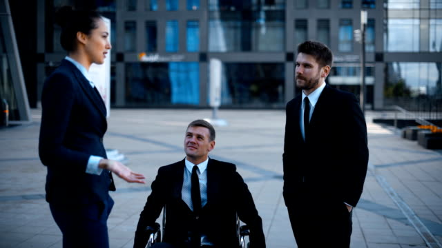 Entrepreneur in wheelchair invalid disabled, but very happy in conversation with his Colleagues video