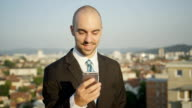 CLOSE UP: Entrepreneur standing on the rooftop, writing messages on smartphone video