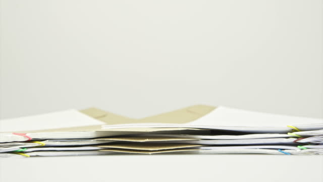 Envelope between stack paper report on table time lapse video