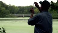 Environmental scientist looking at water sample, silhouette video