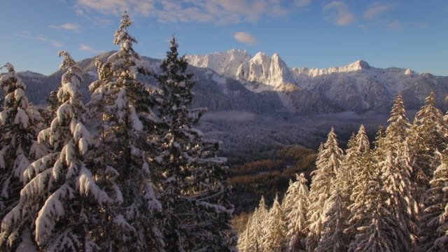 Epic Aerial Dolly of Massive Mountain Peaks Covered in Winter Snow at Sunrise video