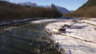Epic Aerial Flying Over Icy River with Fresh Powder Snow to Reveal Mountain Peaks Above Forest Trees video