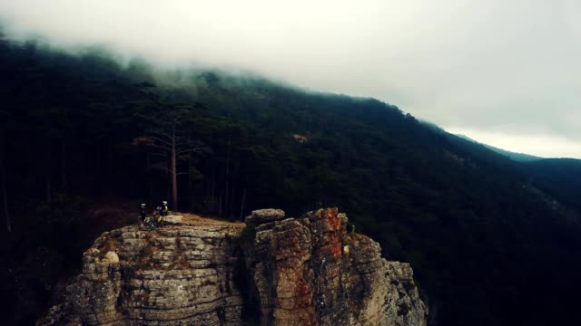 Epic aerial view of mountain bikers standing on mountain in the fog. Cloudy sky, autumn season. Crimea. video