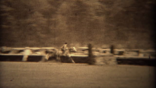 1937: Equestrian horse riding event steeplechase fence jumping event. video