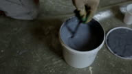 Erector carefully stirs gray paint in plastic pail to apply it on walls video