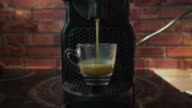 Espresso dripping form automated coffee maker into a cup video