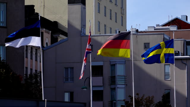 Estonia, UK, Germany and Sweden flags sway on wind, telephoto shot video