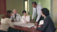 Ethnic Architect Discusses Blueprints with Doctors and Managers video
