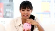 Ethnic businesswoman holding a piggy-bank video