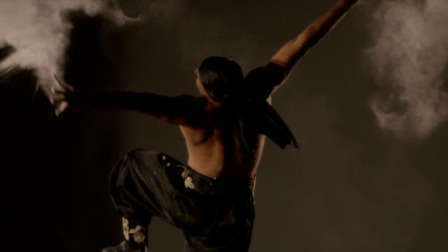 Ethnic Dance. Man dancing with sand on grey background. Shot on RED EPIC DRAGON Cinema Camera in slow motion. video