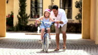 Ethnic Father Teaching Daughter on Bicycle video