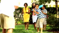 Ethnic mother and father playing baseball with children video