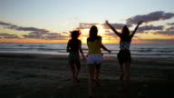 Euphoric girls running towards the sea and getting their feet into the water at sunrise video