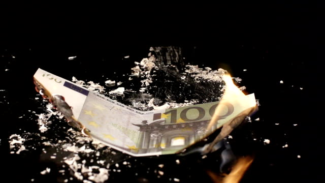 100 euro is flaming and falling on a black table video