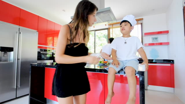 European lady take care of a little Thai boy. Assistance during a photo shoot video