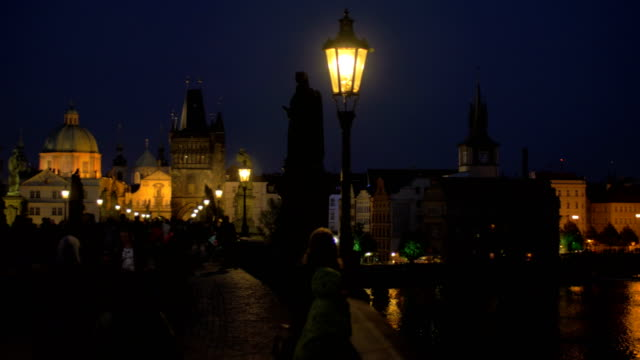 Evening cityscape with walking people on the picturesque Charles Bridge, Prague, Czech Republic video