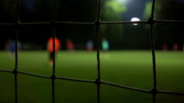 Evening football game slow motion bokeh video. View through mesh video