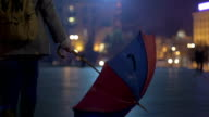 Evening time, woman with unfolded umbrella walking down the street, sadness video
