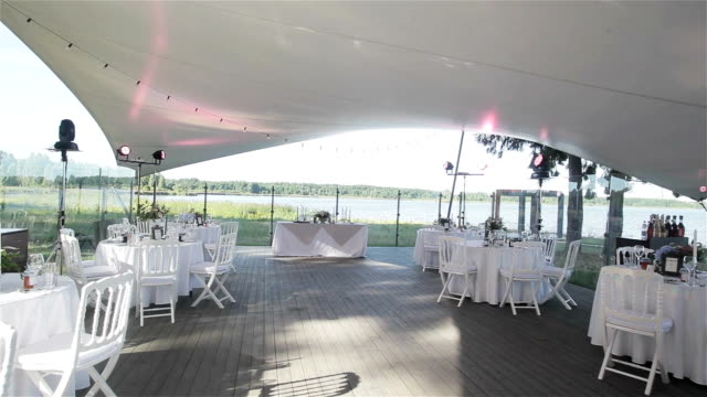 Everything is set and ready for the wedding party in an outdoor restaurant. Wedding reception decoration with all white on summer terrace near the lake. Flycam video
