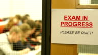 Exam in progress sign with Students behind video